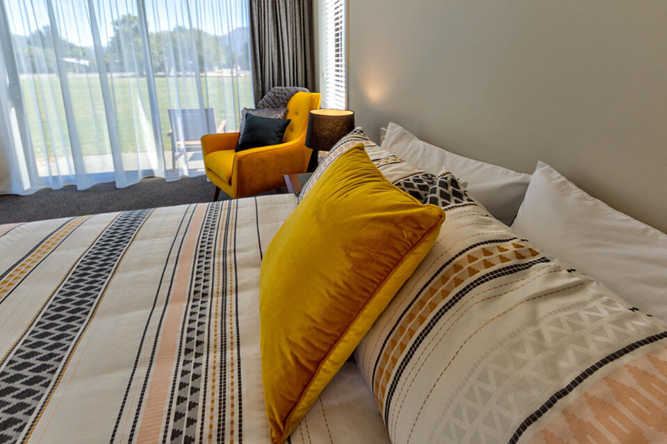 King-sized bed with a yellow and blue patterned bed cover, bed topped with pillows and a bright yellow cushion.
