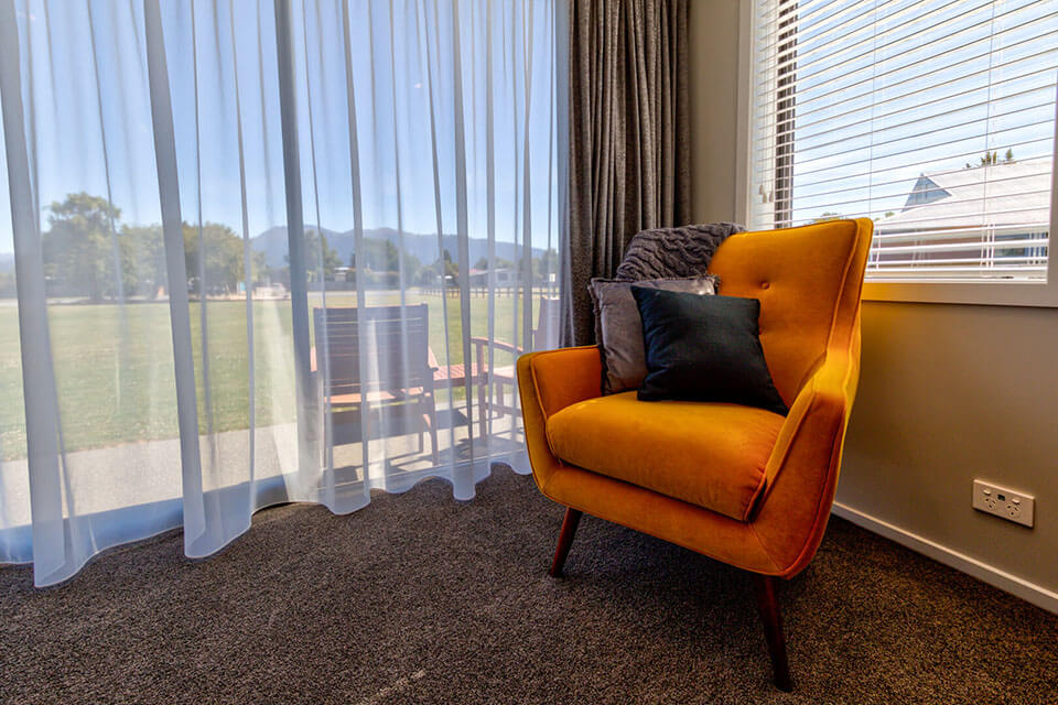 Mustard coloured armchair positioned in the corner of a room adorned with silver and navy coloured cushions.